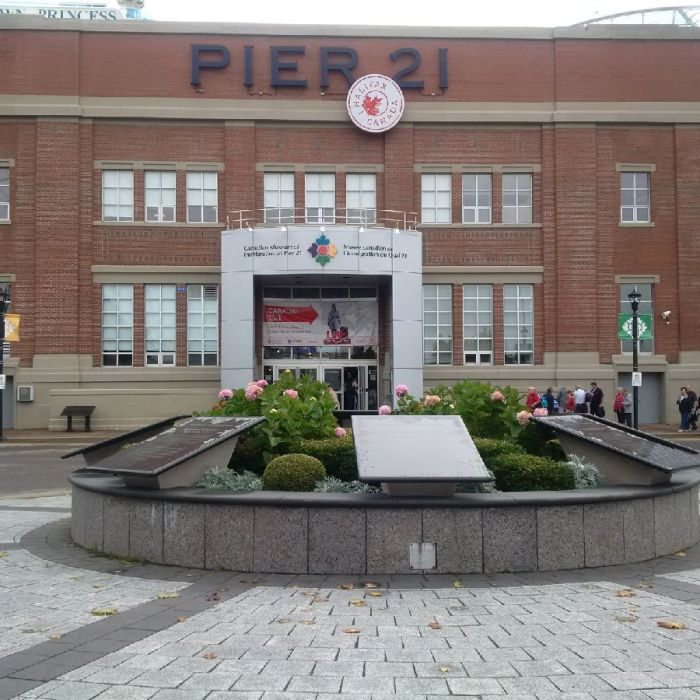 "A colour photograph of a red brick building bearing the sign ""Pier 21."" In front of its main entrance is a raised garden enclosed within a circular stone form that supports several large plaques."