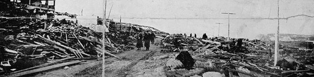A black-and-white photograph of several people walking down a street with destroyed buildings on both sides.